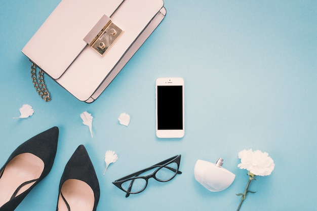 Smartphone with woman shoes and flower on table Free Photo