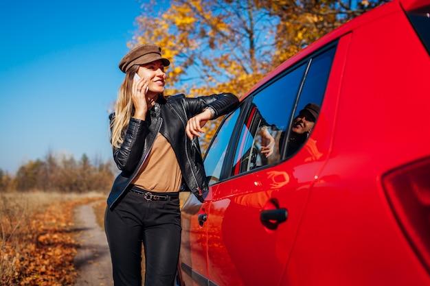 Автомобиль молодой женщины готовя используя smartphone на дороге осени. водитель остановил авто в лесу, чтобы позвонить Premium Фотографии