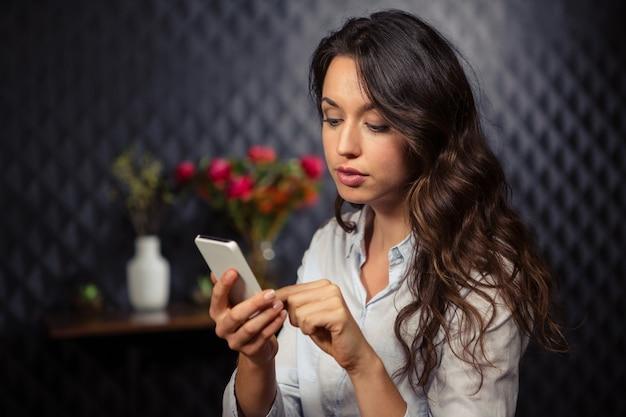 Творческая коммерсантка используя ее smartphone Premium Фотографии