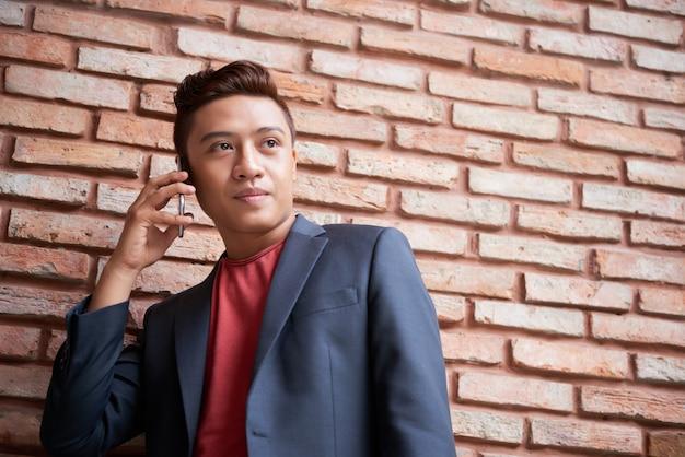 Стильный молодой азиатский человек стоя перед кирпичной стеной и держа smartphone к уху Бесплатные Фотографии