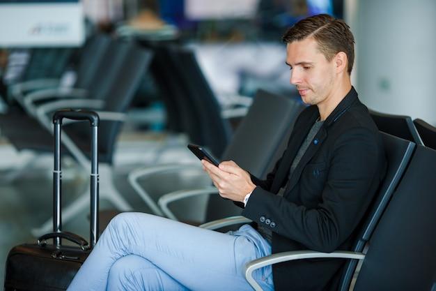Молодой человек с мобильным телефоном внутри в авиапорте. молодой человек с smartphone на авиапорте пока ждущ посадку на борт. Premium Фотографии