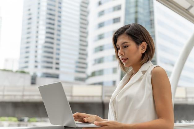 Красивая азиатская девушка усмехаясь в одеждах бизнес-леди используя портативный компьютер и smartphone Бесплатные Фотографии
