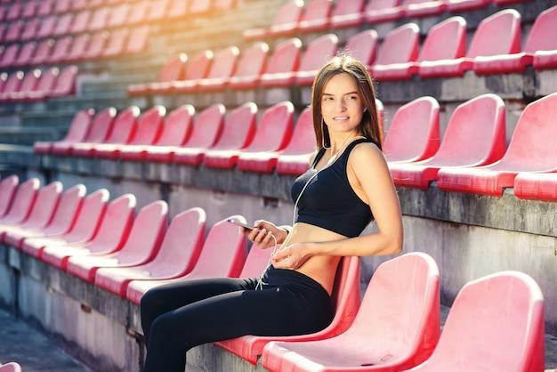 Молодая женщина фитнеса слушая к музыке на smartphone Premium Фотографии