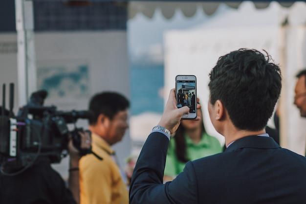 Человек с темными волосами фотографируя людей на smartphone Premium Фотографии