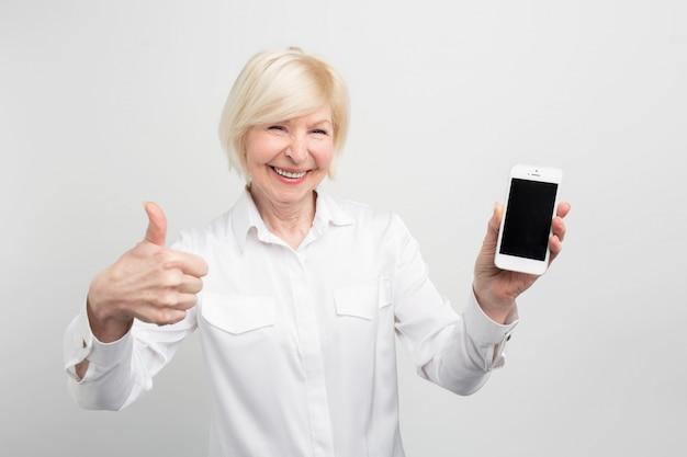 Изображение зрелой женщины с новым smartphone. она проверила его и признала, что этот телефон хороший. вот почему она показывает большой палец вверх. Premium Фотографии