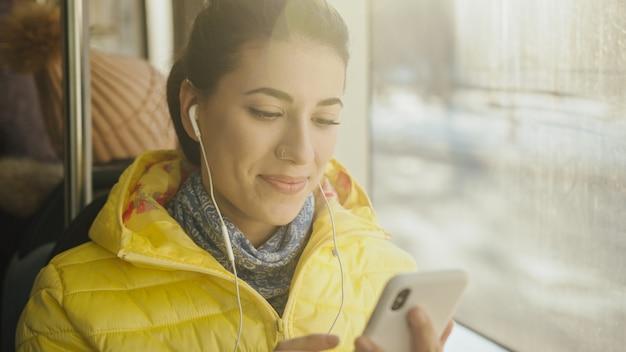Молодая женщина улыбается стоя в поезде, трамвае или автобусе. счастливый женский пассажир слушая к музыке на smartphone в общественном транспорте. Premium Фотографии