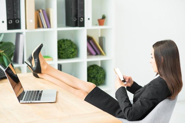 Молодая коммерсантка сидя на стуле с пересеченными ногами на столе используя smartphone Бесплатные Фотографии