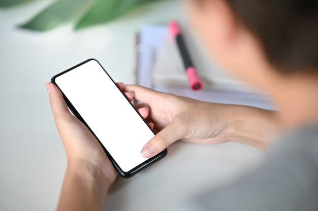 Подрезанные руки съемки используя smartphone модель-макета на столе офиса с путем клиппирования. Premium Фотографии