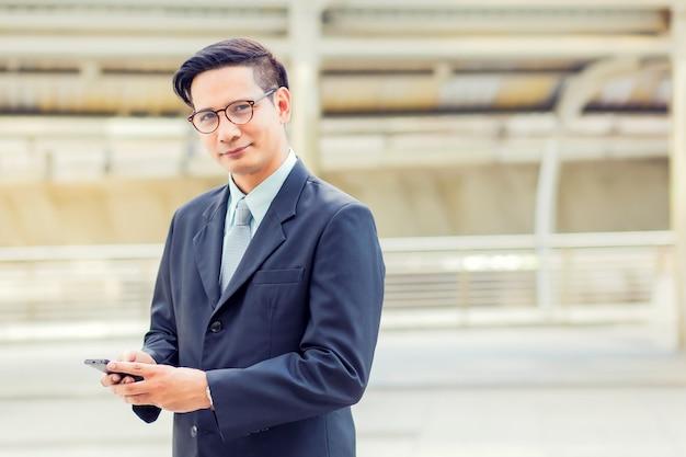 Бизнесмен азии молодой красивый с его smartphone стоя на дорожке современного города. Premium Фотографии