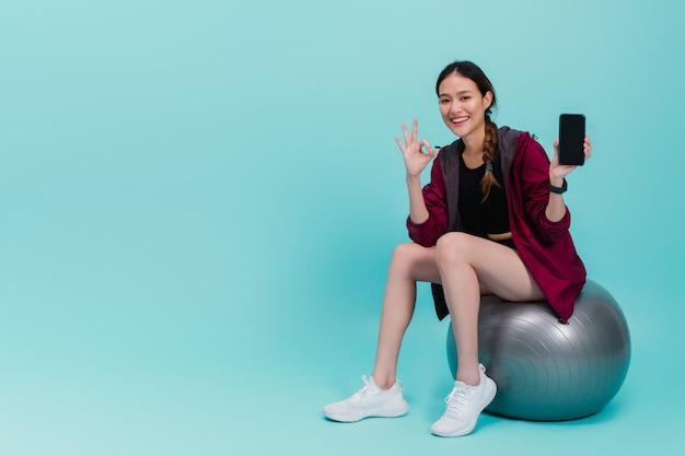 Азиатская красивая счастливая женщина держа smartphone и сидя на шарике пригонки после тренировки изолированной на сини Premium Фотографии