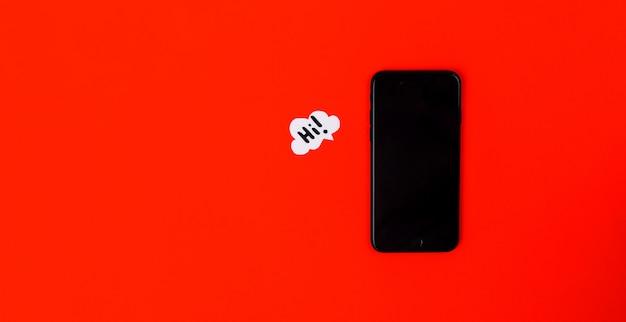 Смартфоны с бумажной речи пузыри на красном фоне. концепция связи. вид сверху. копировать пространство бумажная композиция с текстом hi Premium Фотографии