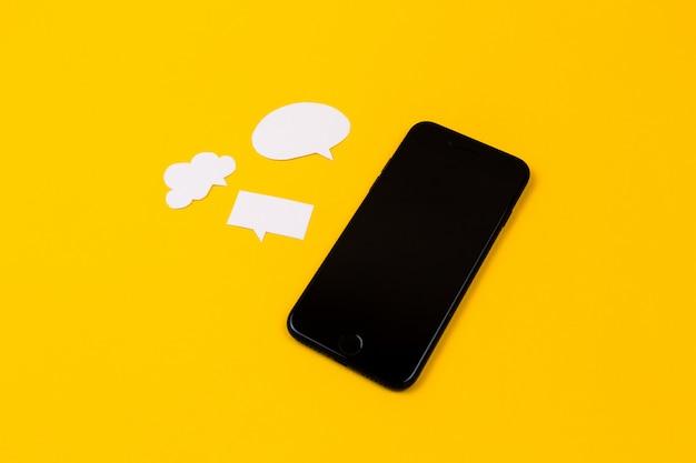 Смартфоны с бумажной речи пузыри на желтом фоне. концепция связи. вид сверху. копировать пространство бумажная композиция Premium Фотографии
