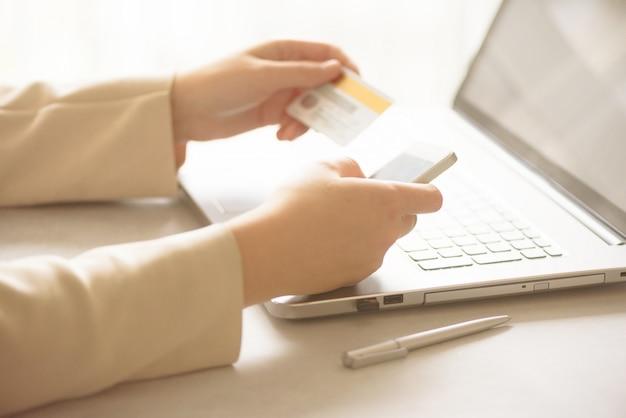 両手クレジットカードとsmatrphone。オンラインショッピング。 Premium写真