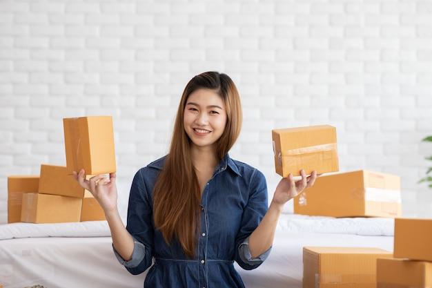 Предприниматель малого и среднего бизнеса молодых азиатских женщин, работающих с ноутбуком для интернет-магазинов на дому, веселый и счастливый с коробкой для упаковки на дому Premium Фотографии