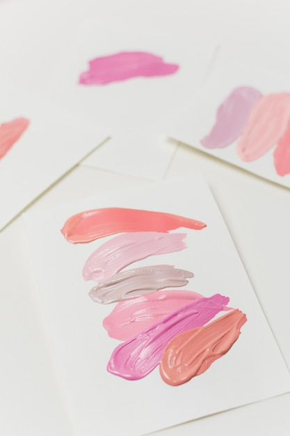 Smears of pastel colors lipstick on paper sheets Free Photo