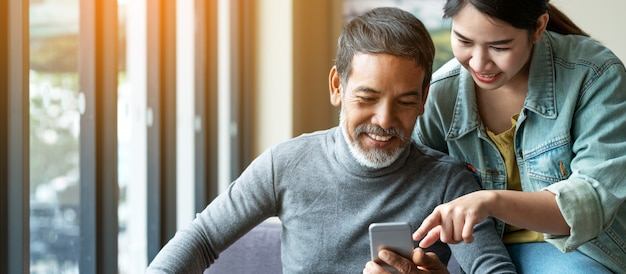 Smile attractive stylish short beard mature asian man using smartphone with young woman. Premium Photo