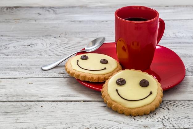 一杯のコーヒー、木製の背景、食品と赤いプレートにクッキーを笑顔します。 無料写真