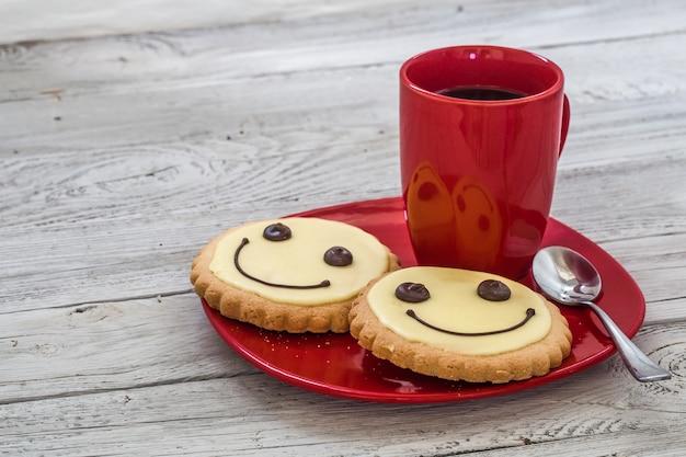 一杯のコーヒー、木製の壁、食べ物と赤いプレート上の笑顔のクッキー 無料写真