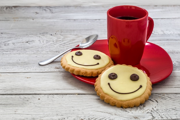 Smile cookies on a red plate with cup of coffee, wooden background, food Free Photo