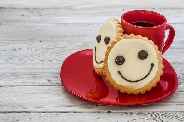 Sorriso biscotti su un piatto rosso con tazza di caffè, parete in legno, cibo Foto Gratuite