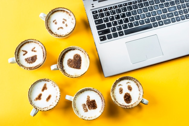 Smile emoji painted on cups of cappuccino next to the laptop Premium Photo