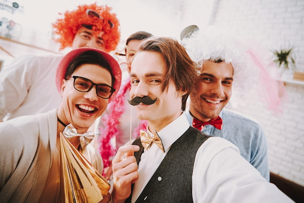 Smile gay guys in bow ties taking selfie on phone at party. Premium Photo