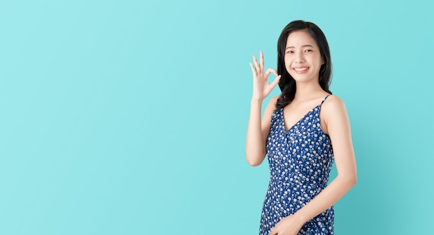 Smile happily asian woman shows ok sign and looking at the camera over blue background. Premium Photo