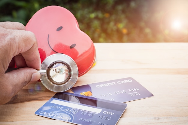 Smile red heart stethoscope on mock up credit card with cardholder in hospital wood desk Premium Photo