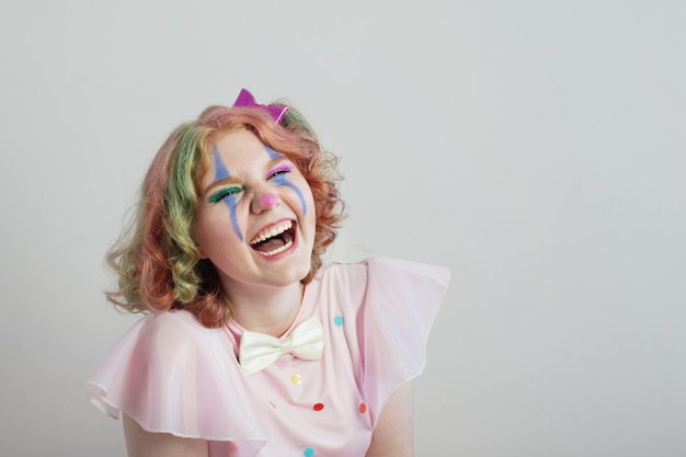 Smile teenager girl in clown costume on gray surface Premium Photo