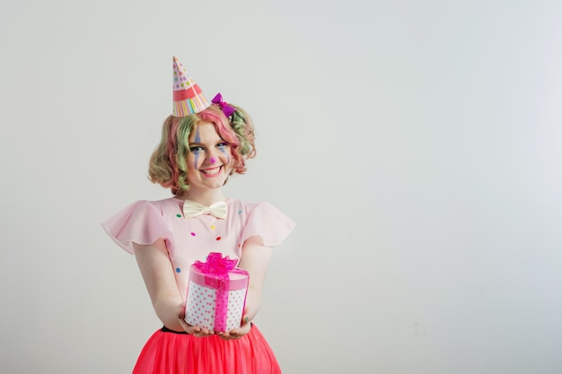 Smile teenager girl in clown costume with box gift Premium Photo
