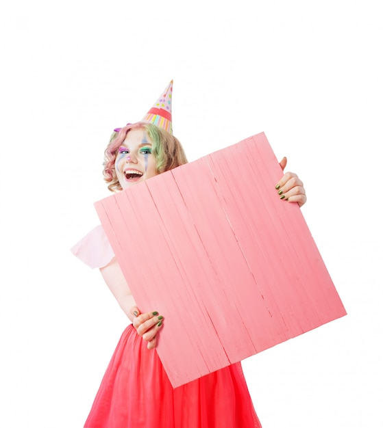 Smile teenager girl in clown costume with writing board Premium Photo