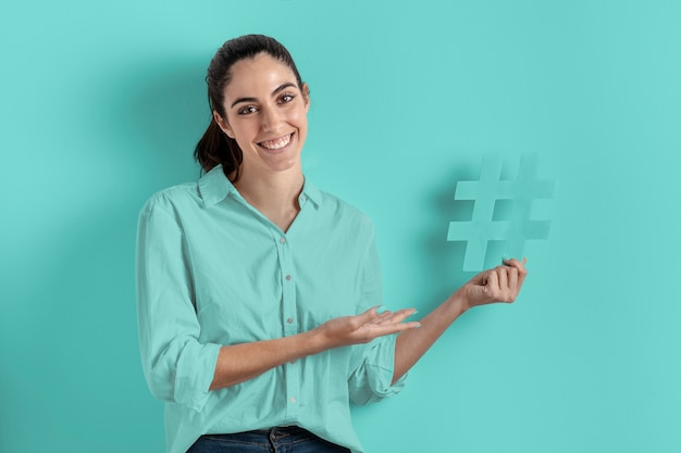 Smile woman holding the hashtag sign Free Photo