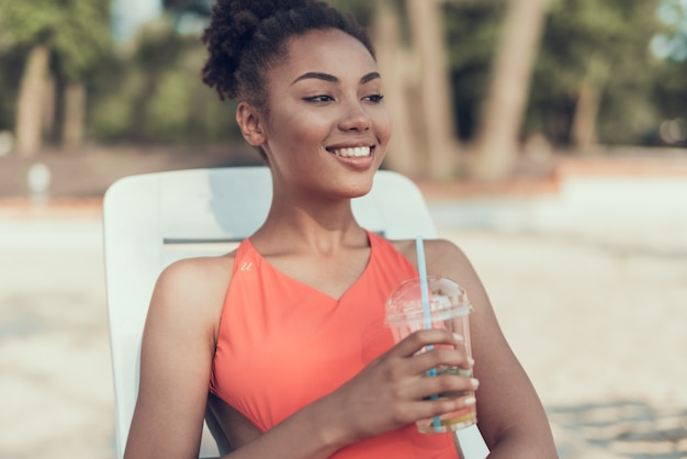 Smile woman is drinking and resting on river Premium Photo