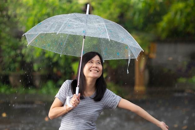 Smile woman in the rain with umbrella Premium Photo