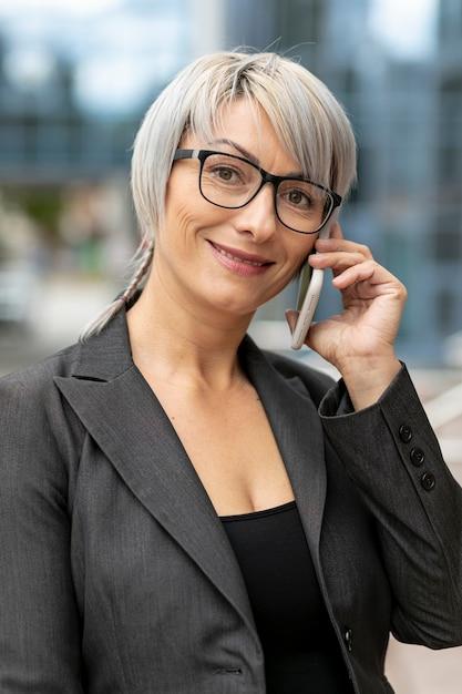 Smile woman talking at phone and looking at camera Free Photo