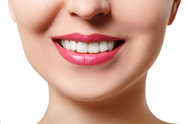 The smile of a young woman with perfect white teeth. close-up isolated on white Premium Photo