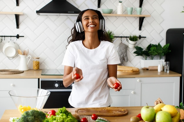 Smiled beautiful mulatto woman is holding tomatoes and listening something in big headphones near the table full of the fresh vegetables on the modern kitchen dressed in white t-shirt Free Photo