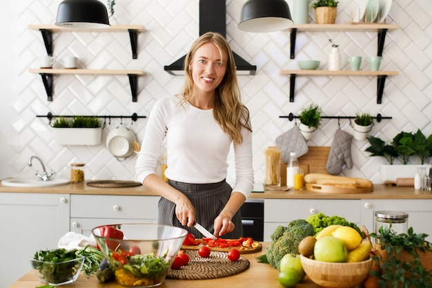 Smiled blonde caucasian woman is cutting red pepper in the modern kitchen on the table full of fresh fruits and vegetables Free Photo