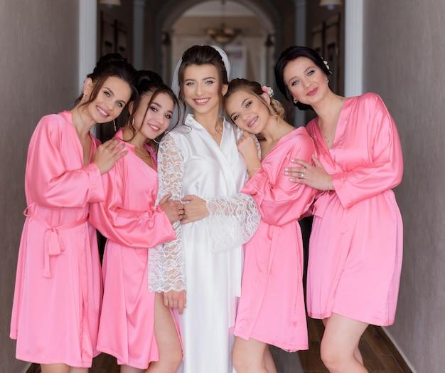 홀에서 아름다운 신부와 분홍색 부드러운 잠옷을 입고 미소 행복한 신부 들러리 무료 사진