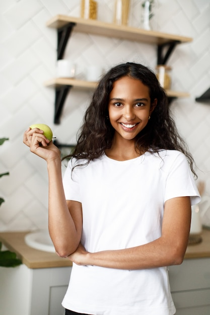 Smiled mulatto woman dressed in white t-shirt, with pretty face and loose hair is holding green apple in hand in the kitchen Free Photo