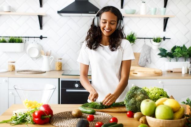 Улыбающаяся женщина-мулатка в больших беспроводных наушниках режет зелень на современной кухне возле стола, полного овощей и фруктов Бесплатные Фотографии