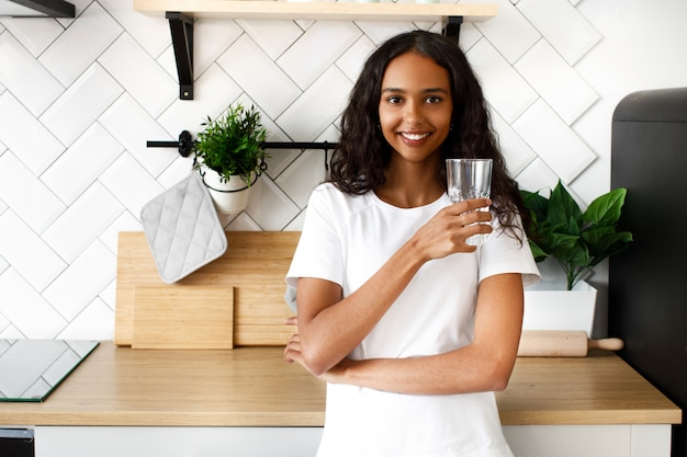 Smiled mulatto woman is holding glass with water near the kitchen desk on the modern white kitchen Free Photo