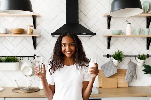 La donna mulatta sorrisa con i capelli sciolti tiene in mano un bicchiere vuoto e un bicchiere di latte vicino allo scrittorio della cucina sulla moderna cucina bianca vestita di t-shirt bianca Foto Gratuite