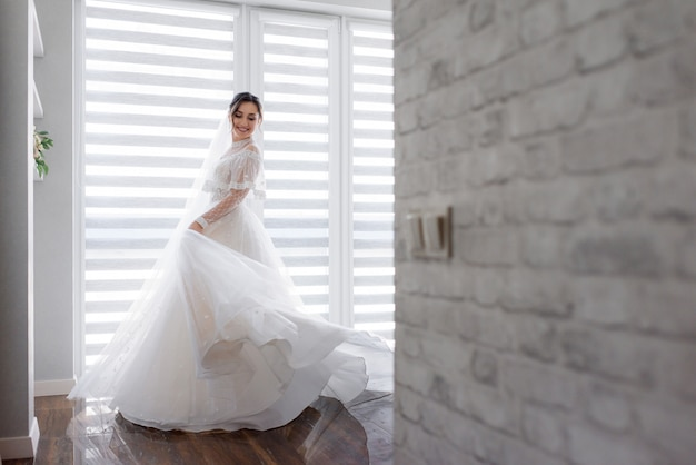 Smiled pretty bride is turning around in room near white brick wall dressed in fashionable dress, wedding fashion Free Photo