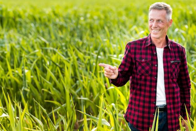 Smiley agronomist indicating sideways Free Photo