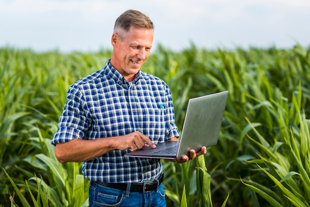 Smiley agronomist using a laptop Free Photo