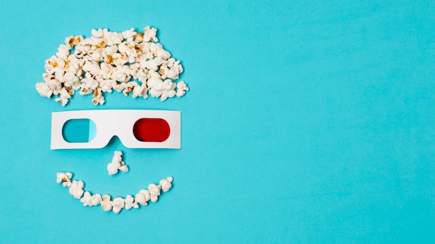 Smiley anthropomorphic face made with popcorns and 3d glasses over the cinema time text Free Photo