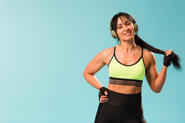 Smiley athletic woman posing in gym outfit with headphones Free Photo