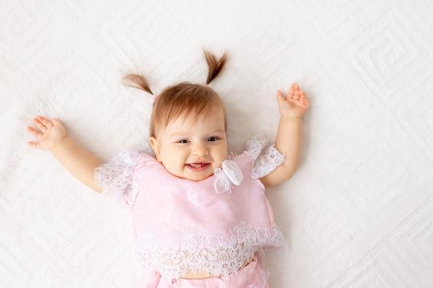 Смайлик девочка сидит на кровати Premium Фотографии