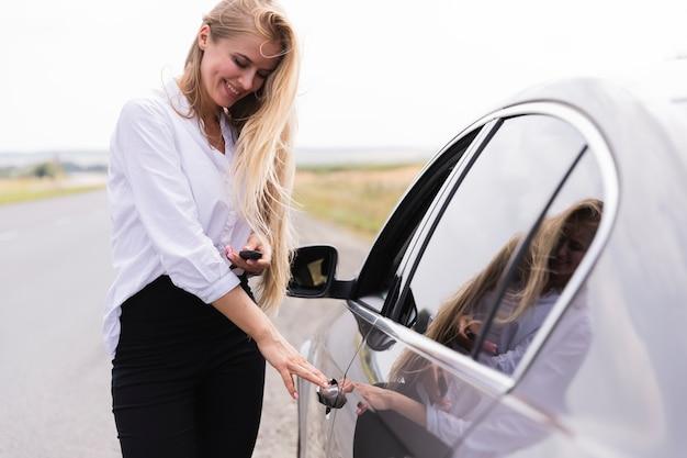 Smiley beautiful woman opening the car door Free Photo